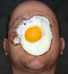 A bald, chubby guy with egg on his face