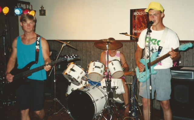 Barry (left) and Rob Petkau, with Dave [Boog] Powell on drums, (hiding behind a cymbal) formed the power trio Stranger. This photo was taken in the Standard, Alberta bar in the summer of 1990 to a small but semi-appreciative crowd of family, friends and local winos.